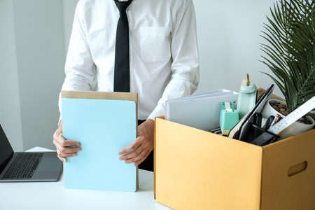 Business man employee packing document and picking up personal belongings into brown cardboard box to leaving workplace when resignation from work or changing work