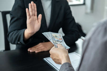 Close up of man employee offering bribe money to businessman to signing the contract to joint engage in illegal and immoral project while he refusing an offer Standard-Bild