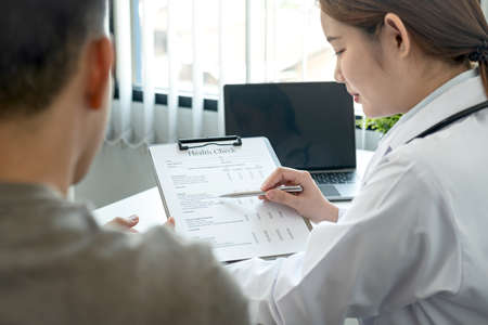 Doctor is pointing on document to explaining disease and symptoms for patient during to talking about diagnostic, medicine and to giving advice to patient in her clinic