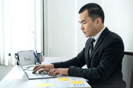 Businessman boss in suit to analysis of investments in new business from chart and document during to typing new idea for business project and financial data while sitting to working in office Standard-Bild