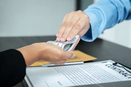 Close up of man employee receiving bribe dollars in his hands from businessman after signing the contract to engage in illegal and immoral project of corruption Standard-Bild