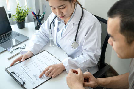 Doctor is pointing on document to explaining disease and illness symptoms for patient before writing a prescription and giving treatment advice to patient in her clinic