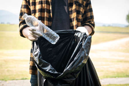 Close up of volunteer man in gloves to picking up plastic bottle into plastic black bag for cleaning the park during environmental activity to collecting garbage