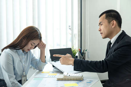 Businessman boss in suit scolding and pointing to woman office worker about bad work of her while she is sitting to stress and bow down in the office