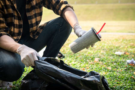 Volunteer man in gloves sitting to picking up coffee cup into plastic black bag for cleaning the park during environmental activity to collecting garbage