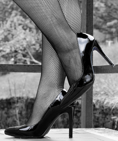 Sexy legs in black high heels and fishnet stockings