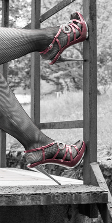 Sexy legs in red high heels and fishnet stockings Stock Photo