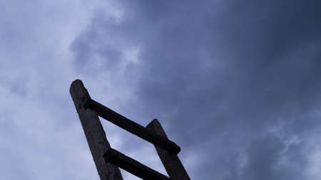 Wooden staircase leading to the blue sky with fluffy clouds