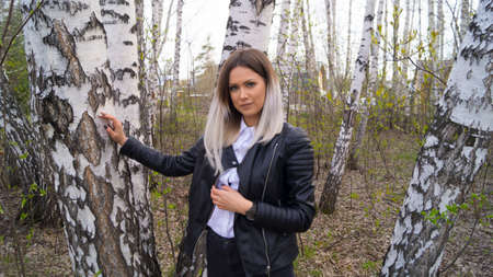 Beautiful young girl in a birch forest in the spring, the trees have just started to bloom