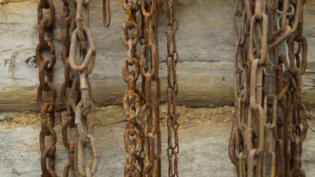 Old rusting chains hang on the wooden log wall of the house