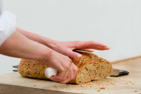unsliced: Hands cutting bread Stock Photo