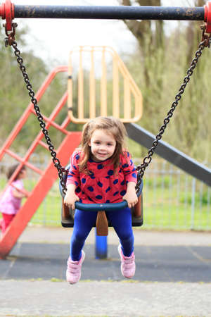 back and forth: Young child on a swing Stock Photo