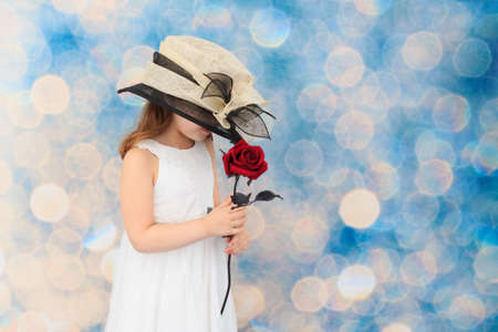 red rose bokeh: Child wearing an oversized hat, holding a red rose Stock Photo