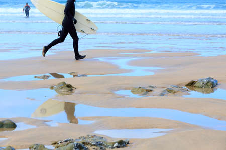 Surfer running on the beach photo