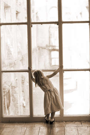 Little girl looking out a large window