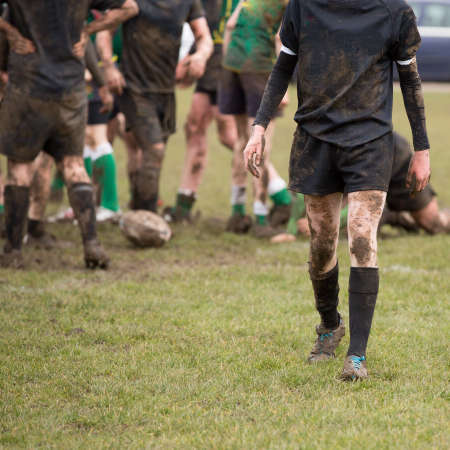 Rugby players in muddy game of rugby