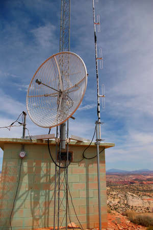 Communication site on hilltop with view of mountains.