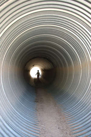 Child walking in a culvert under the road. photo