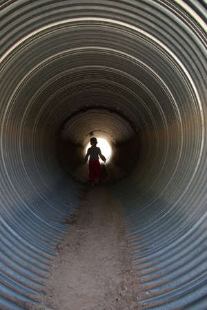 Child walking in a culvert under the road. Imagens - 929304