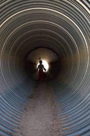 culvert: Child walking in a culvert under the road.