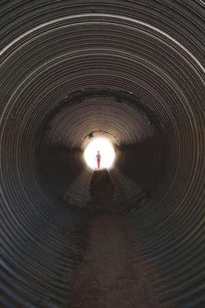 culvert: Small person exiting a culvert under a road.