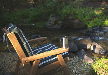 Outdoor chair and morning coffee cup by mountain stream.