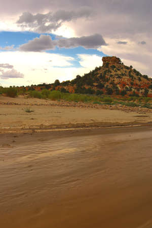 Wet mud flat with butte and clouds in background. Stock Photo