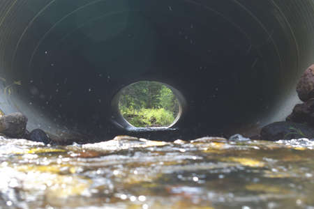 culvert: Water rushing through a culvert under a road. Stock Photo