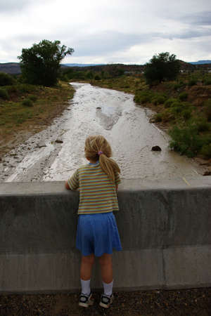 Small child looking into a wash over the edge of a barrier.