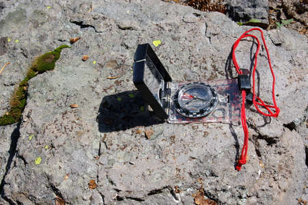 Small compass with red lanyard on rock in forest.