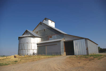 Silver barn with open door against a bright blue sky. Stock Photo