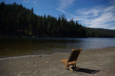 Small wooden chair at a beach on a mountain lake.