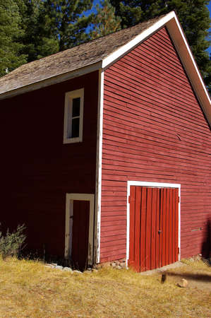 Two story red barn with two doors and a window.