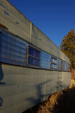 Old travel trailer parked in the weeds at sunset. Imagens - 2137076