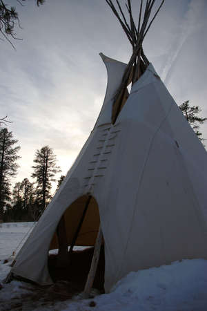 Canvas teepee in the snow at sunset.
