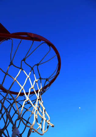 Basketball hoop with a clear blue sky and a small white moon.