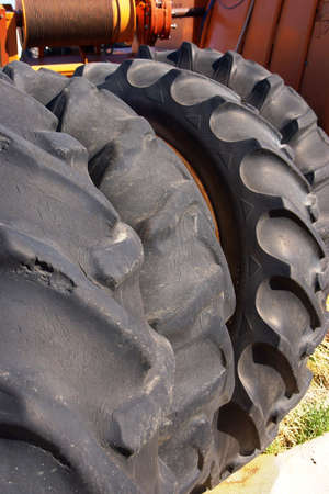 Four old tractor tires stacked against an implement.