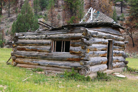 Old cabin with a collapsed roof in a remote area. Stock Photo - 3379844
