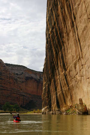 Schipper poedelbad een kajak onder een grote stenen muur in een rivier canyon. Stockfoto