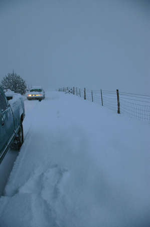 Two vehicles on a ranch road during a snow storm. Stock Photo - 4068493