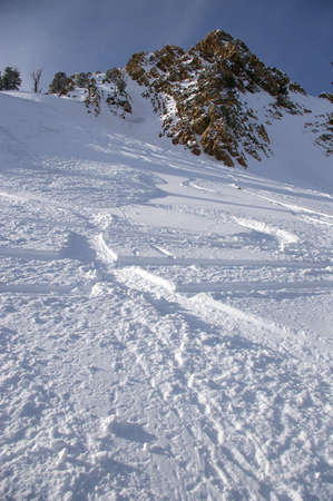 Ski tracks carving through a steep snow field below a mountain peak.