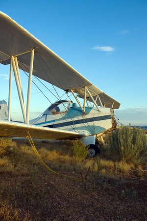 An old crop-dusting bi-plane abandoned in an overgrown field.