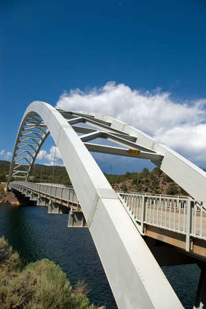 An arched highway bridge spanning a small lake with a storm in the sky. Stock Photo