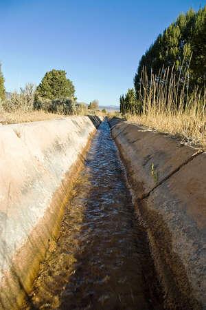 Een open cement kanaal met irrigatie water stroomt.