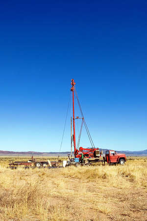 drilling well: A well drilling rig in an empty field.