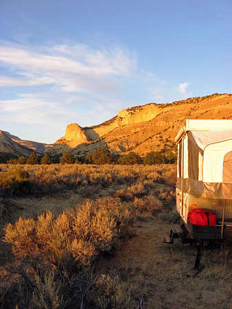 A small camp trailer parked in a desert area near a cliff wall. photo