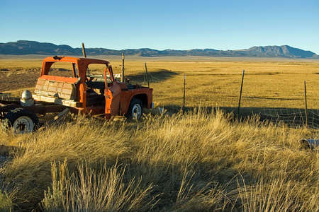 Derelict truck and empty fields on an abandoned farm. photo