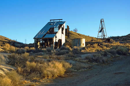 mine site: Rusting equipment and broken buildings at an abandoned mine site. Stock Photo