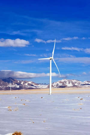 A lone wind turbine stands in a high desert environment. Stock Photo