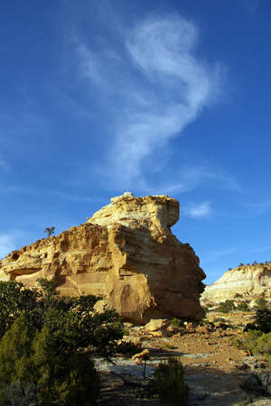 hoodoo: A sandstone hoodoo in the desert with a swirling cloud above.